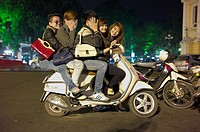 Five young adults cram onto one scooter on the streets of Vietnam at night