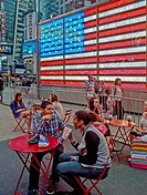 People relax at outdoor tables in Times Square, New York City  In background is the electric United States flag on the wall of a military recruiting c...
