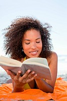 Young woman lying on her beach towel while concentrating and reading a book