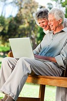 A couple are smiling at a laptop