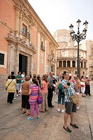 Group of tourists in the Plaza de la Virgen, Valencia old town, Spain