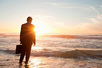 Businessman watching the waves at his feet while holding a case on a beach