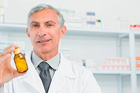 Pharmacist holding a bottle full of pills with one hand in the pharmacy of a hospital