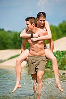 Piggyback _ happy couple enjoy sun at lake