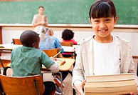 Smiling elementary student holding pile of books in classroom