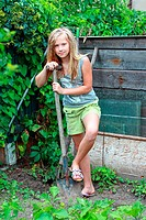 A 12 year old girl standing with a spade in the garden