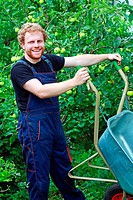 A young gardener working in the garden and holding the wheelbarrel