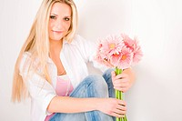 Young woman hold pink gerbera daisy flower