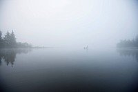 Fisherman in the fog in early morning at Lake Umbagog, New Hampshire, USA