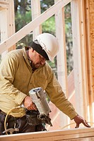 Carpenter using a nail gun on studs