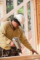 Carpenter using a nail gun on studs