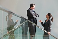 Hispanic businesswoman talking with a businessman on stairwell in office building