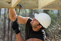 Hispanic carpenter nailing pressure treated deck joist with hammer