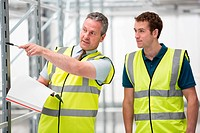 Two men in warehouse, one pointing with pen