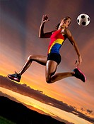 Female footballer in mid air against sunset