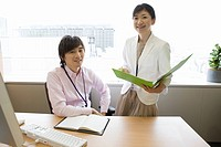 Businessman and businesswoman smiling at office