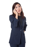 Studio portrait of mid adult Asian business woman talking on her cell phone and looking thoughtful on white background
