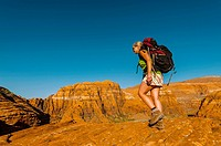 Woman backpacking in the red rock formations of Snow Canyon State Park near St  George, Utah USA