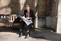 Mature businessman sitting on bench reading newspaper