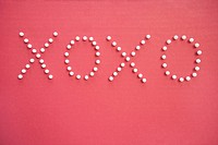 Close_up of push pins in formation of x and o over pink background depicting hugs and kisses
