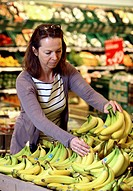 Fruit section, woman shopping for bananas, self-service, food department, supermarket, Germany, Europe