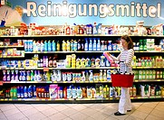 Woman looking at cleaning products in a corridor with household goods while shopping in a self-service grocery department, supermarket, Germany, Europ...
