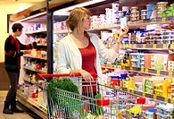 Female customer standing in front of the refrigerated shelf, dairy products, food hall, supermarket, Germany, Europe