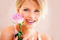 Portrait of a young woman holding a single pink rose