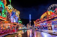 Ghost train, bumper cars and the No Limit XXL funfair ride at night after a heavy shower, Suedring amusement park, Innsbruck, Tyrol, Austria, Europe