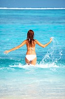 Rear view of young woman playing while splashing water on beach