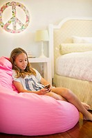 Hispanic girl text messaging on cell phone in bedroom