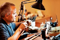 Jeweler using a blowtorch in his wrokplace