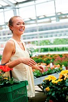 Copyspace_ attractive young ethnic woman standing with basket of flowers on arm laughing in nursery