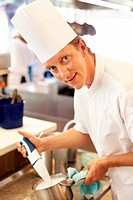 Portrait of handsome young chef working in kitchen with hand blender