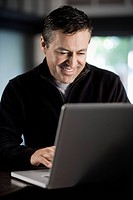 Hispanic businessman typing on laptop