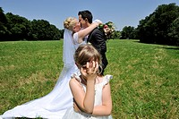 Wedding, young couple kissing, little coy girl covering her eyes