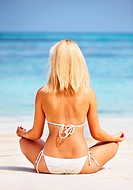 Rear view of Caucasian woman meditating at beach
