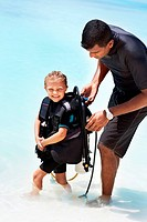 Little girl having her diving equipment checked by an instructor