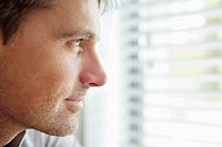 Close_up of a man looking through a window and thinking