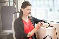 Woman traveling in a bus and using a mobile phone