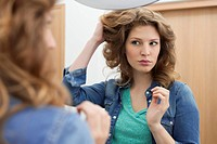 Woman examining her hair (thumbnail)