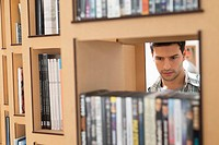 Man choosing books from a bookshelf (thumbnail)
