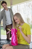 Happy woman opening a present given by her boyfriend (thumbnail)