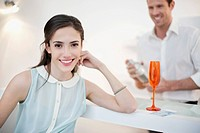 Woman smiling with her husband shaking cocktail in the background