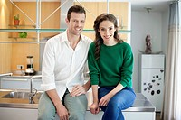 Couple sitting on the kitchen counter and smiling