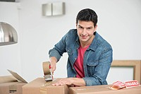 Man taping up a cardboard box (thumbnail)