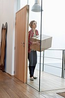 Woman carrying a cardboard box at home (thumbnail)