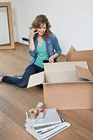 Woman talking on a mobile phone near cardboard boxes (thumbnail)
