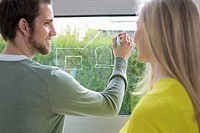 Woman looking at an architect drawing a design on the window glass (thumbnail)