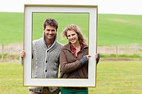Portrait of a couple holding a frame in a field